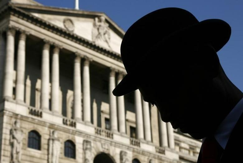 An actor in a bowler hat is silhouetted in front of the Bank of England in central London September 19, 2008. REUTERS/Luke MacGregor/Files