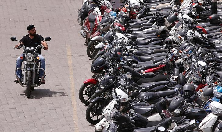 A man rides a motorcycle in a parking lot at a market in New Delhi, June 16, 2016. REUTERS/Adnan Abidi/Files