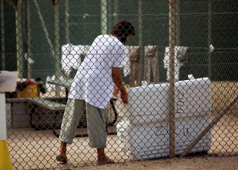In this photo, reviewed by the U.S. Military, a Guantanamo detainee opens a cooler inside the open yard at Camp 4 detention center, at the U.S. Naval Base, in Guantanamo Bay, Cuba, January 21, 2009. REUTERS/Brennan Linsley/Pool