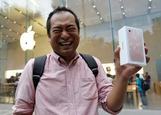 9月16日、NTTドコモ、KDDI(au)、ソフトバンクの携帯電話大手3社は16日、米アップルの新型スマートフォン「iPhone(アイフォーン)7」と「7プラス」を発売した。写真はアップルストア表参道店で買ったばかりの「iPhone(アイフォーン)7」を見せる購入者(2016年 ロイター/Issei Kato)