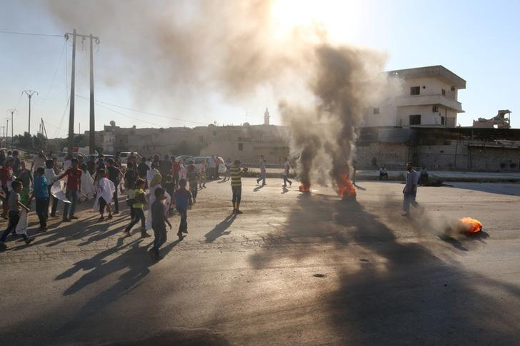 People gather near burning tyres during a demonstration against forces loyal to Syria's President Bashar al-Assad and calling for aid to reach Aleppo near Castello road in Aleppo, Syria, September 14, 2016. REUTERS/Abdalrhman Ismail