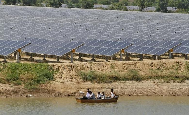 Security personnel sit in a boat as they patrol the premises of a newly inaugurated solar farm at Gunthawada village in Banaskantha district in Gujarat October 14, 2011. REUTERS/Amit Dave/Files