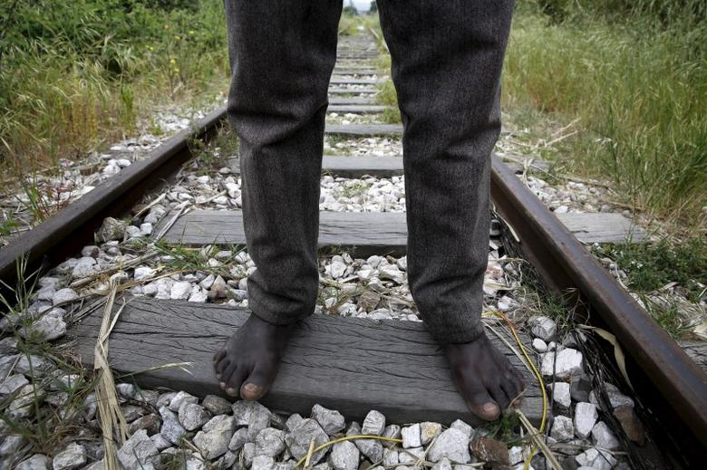26-year-old Azam from South Sudan stands on rail tracks after failing to flee to Italy in the western Greek town of Patras April 28, 2015. REUTERS/Yannis Behrakis