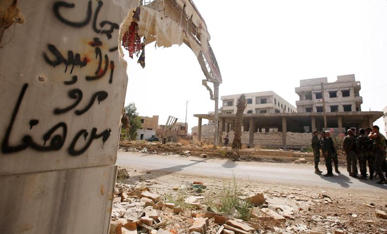 Syrian army soldiers stand at the entrance of the besieged Damascus suburb of Daraya, before the start of evacuation of residents and insurgents of Daraya, Syria August 26, 2016. The Arabic on the wall reads, ''Assad's men passed from here''. REUTERS/Omar Sanadiki