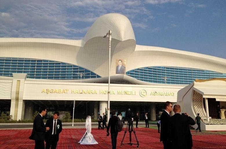 People stay in front of the terminal of the newly built airport with a portrait of Turkmen President Kurbanguly Berdymukhamedov seen in the background during its official opening in  Ashgabat, Turkmenistan, September 17, 2016.  REUTERS/Marat Gurt