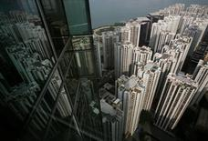 Жилые кварталы отражаются в оконном стекле бизнес-центра  в Гонконге. Китайский город Шэньчжэнь неожиданно уступил лидерство по темпам роста цен на жильё в августе, но вместе с другими городами всё же показал быстрый рост стоимости недвижимости.   REUTERS/Bobby Yip/File Photo