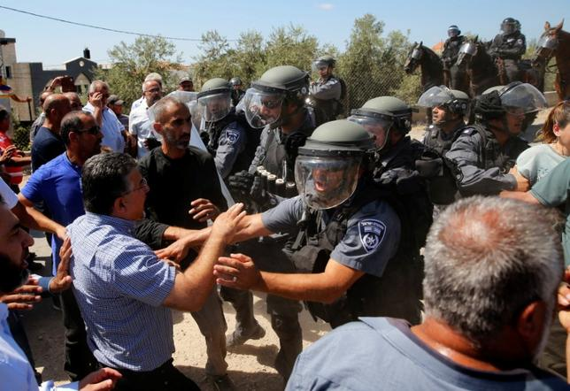 Israeli policemen scuffle with Arab Israelis during a demonstration held by Israeli right-wing protesters (not pictured) near the family home of Nashat Melhem, an Arab Israeli who killed three people in a Jan. 1 shooting attack, in the northern Arab Israeli village of Arara September 19, 2016. REUTERS/Ammar Awad