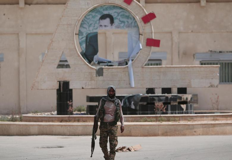 A Kurdish fighter from the People's Protection Units (YPG) carries his weapon as he walks at the faculty of economics where a defaced picture of Syrian President Bashar al-Assad is seen in the background, in the Ghwairan neighborhood of Hasaka, Syria, August 22, 2016. REUTERS/Rodi Said/File Photo