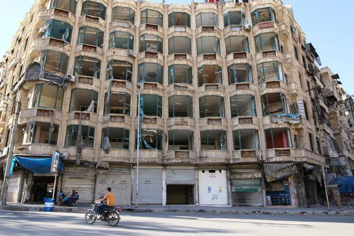 A man rides a motorcycle past a damaged building in the rebel-held al-Shaar neighbourhood of Aleppo, Syria, September 17, 2016. REUTERS/Abdalrhman Ismail
