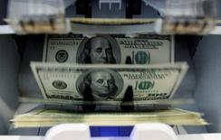 Em foto de arquivo, notas de dólar são contadas por máquina em banco em Berna, Suíça 15/08/2011 REUTERS/Pascal Lauener