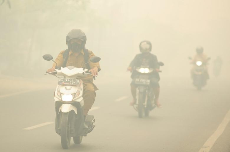 People ride motorcycles as haze shrouds the street in Palangkaraya, Central Kalimantan province, Indonesia October 27, 2015  in this picture taken by Antara Foto.    REUTERS/Jessica Helena Wuysang/Antara Foto