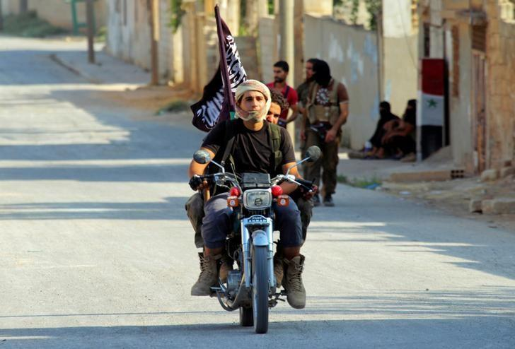 Rebel fighters from the hardline jihadist Jund al-Aqsa ride on a motorbike in Taybat al Imam town after they advanced in the town in Hama province, Syria August 31, 2016. REUTERS/Ammar Abdullah/File Photo