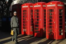 A man passes a row of traditional telephone boxes in London January 15, 2015. British regulator Ofcom has said it would set up a safeguard to make sure BT maintains a sufficient margin between its wholesale and retail superfast broadband charges to allow rival providers to profitably match its prices.  REUTERS/Luke MacGregor  (BRITAIN - Tags: SOCIETY BUSINESS TELECOMS TRAVEL) - RTR4LKOP