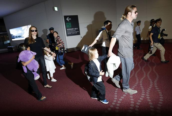 Hollywood actors Brad Pitt (R) and actress Angelina Jolie (2nd L) arrive with their children Knox (2nd R), Vivienne (3rd L) and Pax (L) at Haneda international airport in Tokyo July 28, 2013. REUTERS/Issei Kato