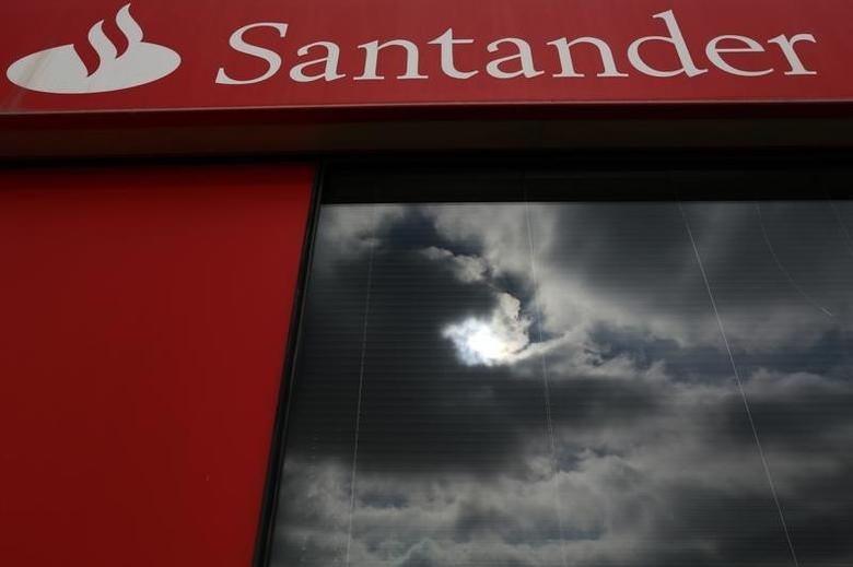 Clouds are reflected onto a Banco Santander branch in Tomares, near Seville September 10, 2014. REUTERS/Marcelo del Pozo