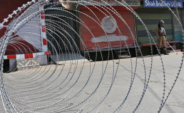 An Indian policeman stands guard next to concertina wire laid across a road during a curfew in downtown Srinagar, India, September 20, 2016. REUTERS/Danish Ismail