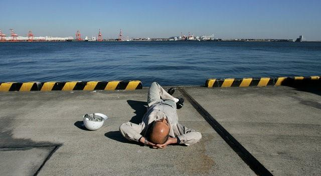 A worker takes a break at a container yard at Ooi Wharf in Tokyo November 21, 2008.   REUTERS/Yuriko Nakao/File Photo