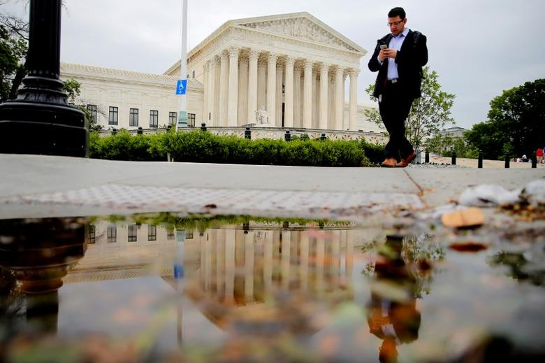 A pedestrian walks in front of the U.S. Supreme Court building in Washington, U.S. May 19, 2016.  REUTERS/Carlos Barria/File Photo