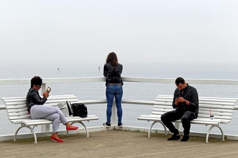 People use mobile phones on the pier at Orlowo beach in Gdynia, Poland September 10, 2016. REUTERS/Radu Sigheti
