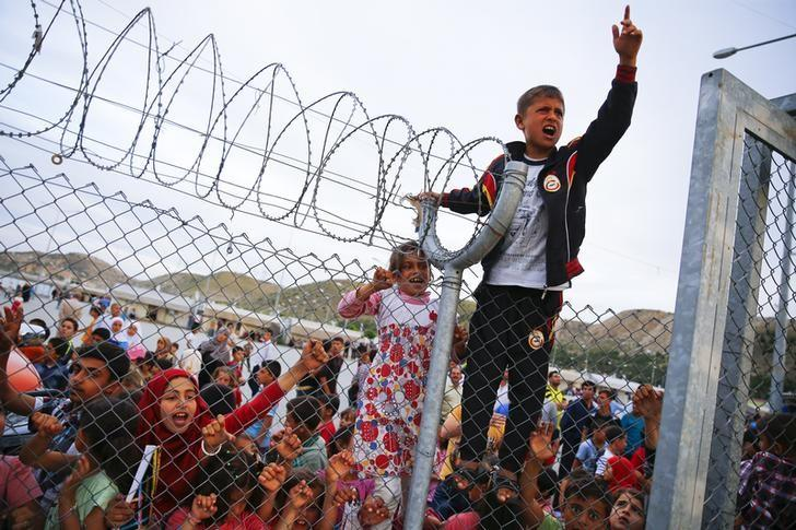 Refugee youths gesture from behind a fence as German Chancellor Angela Merkel, Turkish Prime Minister Ahmet Davutoglu, EU Council President Donald Tusk and European Commission Vice-President Frans Timmermans (all not pictured) arrive at Nizip refugee camp near Gaziantep, Turkey, April 23, 2016. REUTERS/Umit Bektas/File Photo