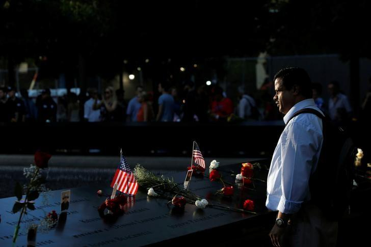 Wbillgates Annaswamy of New York looks in to the south reflecting pool at the National September 11 Memorial and Museum on the 15th anniversary of the 9/11 attacks in Manhattan, New York, U.S., September 11, 2016.  REUTERS/Andrew Kelly