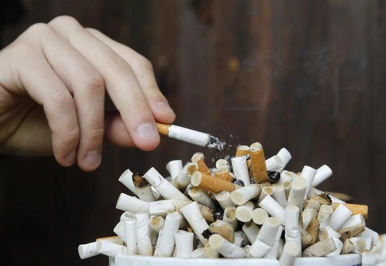 A man taps ashes off his cigarette into an ashtray filled with cigarette butts on a table in Ljubljana October 17, 2012.  REUTERS/Srdjan Zivulovic
