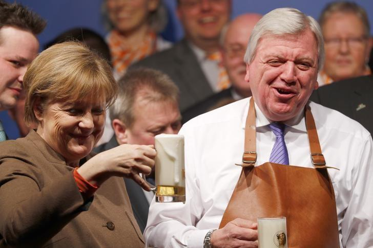 German Chancellor Angela Merkel and Hesse's state Premier Volker Bouffier (R) toast with beer during the Christain Democratic Union (CDU) politial Ash Wednesday meeting in Volkmarsen, Germany February 29, 2016.   REUTERS/Kai Pfaffenbach