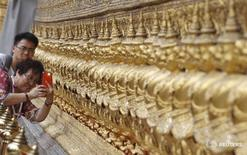 Туристы из Китая в храме Ват Пхракэу в Бангкоке 23 марта 2015 года. Столица Таиланда Бангкок опередила Лондон, став самым популярным туристическим направлением в этом году, согласно ежегодному рейтингу, составляемому оператором платежных карт Mastercard и опубликованному в четверг. REUTERS/Chaiwat Subprasom