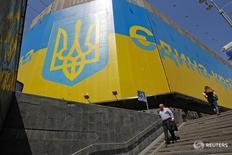People walk near a board displaying the Ukrainian coat of arms in Kiev May 27, 2014. REUTERS/Valentyn Ogirenko (UKRAINE - Tags: SOCIETY) - RTR3R2IR
