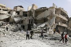 Люди исследуют разрушенное здание после бомбардировки районов Алеппо. Бомбардировка удерживаемых повстанцами восточных районов Алеппо ночью унесла жизни 45 человек, сказал Рейтер директор больницы Аль-Кудс Хамза аль-Хатыб в четверг. REUTERS/Abdalrhman Ismail