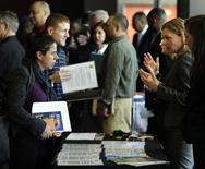 Una representante de la firma Hogan Lovells habla con una persona durante una feria de trabajos en Washington. 9 de abril de 2014. El número de estadounidenses que pidieron el subsidio por desempleo cayó inesperadamente la semana pasada, lo que sugirió que el mercado laboral continúa ganando impulso. REUTERS/Gary Cameron