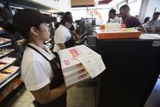 An employee holds boxes of donuts ready for pick up at a newly opened Dunkin' Donuts store in Santa Monica, California September 2, 2014. REUTERS/Mario Anzuoni
