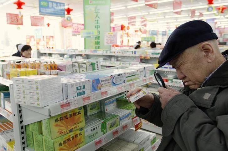 An elderly man uses a magnifier to see the descriptions on a pack of medicine at a pharmacy in Dandong, Liaoning province March 30, 2011. REUTERS/Jacky Chen/File Photo