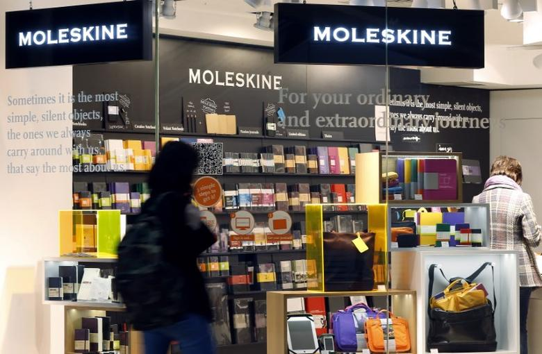 A woman walks past a Moleskine store in Milan April 3, 2013. Shares in upmarket notebook maker Moleskine made a lacklustre debut in Milan on Wednesday as growth concerns and broad market weakness weighed on this year's first major stock listing in crisis-hit Italy. REUTERS/Alessandro Garofalo