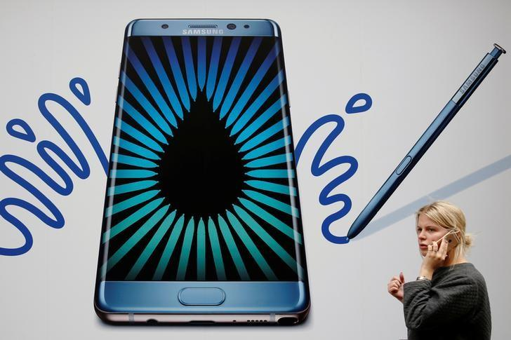 A woman speaks on an Apple phone as she passes an advert for the Samsung Galaxy Note 7 in London, Britain, September 2, 2016.  REUTERS/Luke MacGregor/File Photo