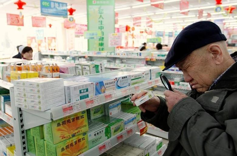 An elderly man uses a magnifiying glass to see the description on a pack of medicine at a pharmacy in Dandong, Liaoning province, China, March 30, 2011.  REUTERS/Jacky Chen/File Photo