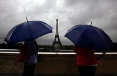 Turistas con paraguas miran la torre Eiffel, en París, Francia. 19 de julio de 2011. La economía de Francia se frenó en el segundo trimestre por primera vez desde principios de 2013, golpeada por una caída del gasto de los consumidores, lo que supone un revés para el presidente François Hollande antes de las elecciones de abril de 2017. REUTERS/Eric Gaillard/File Photo