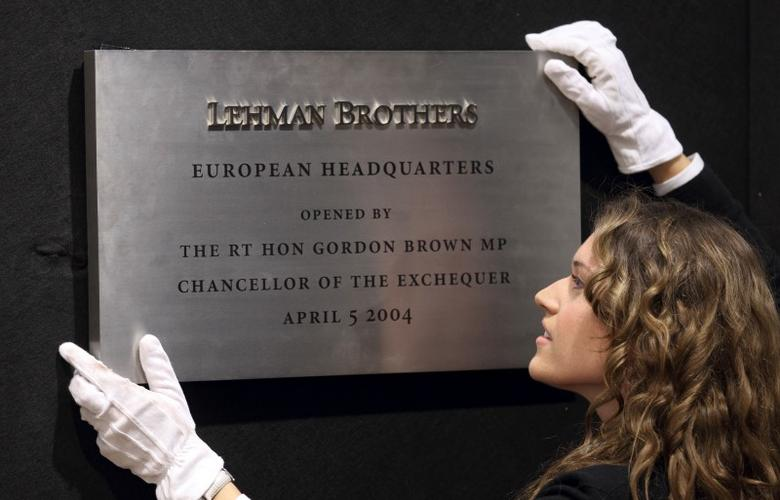 A Christie's employee poses for a photograph with the plaque from Lehman Brothers' European headquarters at Christie's in central London, September 24, 2010.  REUTERS/Andrew Winning