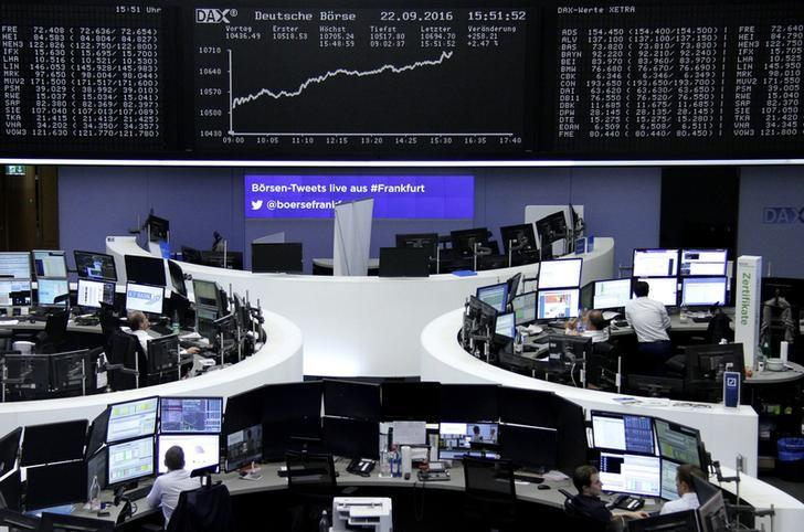 Traders work at their desks in front of the German share price index, DAX board, at the stock exchange in Frankfurt, Germany, September 22, 2016. REUTERS/Staff/Remote