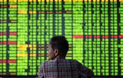 Un inversor mira una pantalla con información bursátil, en una correduría en Hangzhou, China. 12 de septiembre de 2016. Las acciones chinas cayeron casi un 2 por ciento el lunes a un mínimo en siete semanas, lastradas por unos declives en el sector inmobiliario. China Daily/via REUTERS
