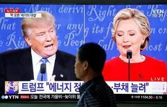 Мужчина проходит в Сеуле мимо телеэкрана, на котором транслируются дебаты в США между кандидатами в президенты Хиллари Клинтон и Дональдом Трампом. 27 сентября 2016 года. Трамп сказал, что США не могут нести бремя решения глобальных проблем и тратиться на защиту таких союзников как Япония. REUTERS/Kim Hong-Ji