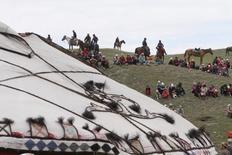 Люди на национальном фестивале у озера Тулпар-Куль в горной гряде Чон-Алай, Ошская область, Киргизия, 25 июля 2015 года. Международный валютный фонд повысил прогноз роста экономики Киргизии в 2016 году до 2,3 процента с 2,2, сообщил глава миссии МВФ в четверг, высказав озабоченность ростом внешнего долга. REUTERS/Vladimir Pirogov