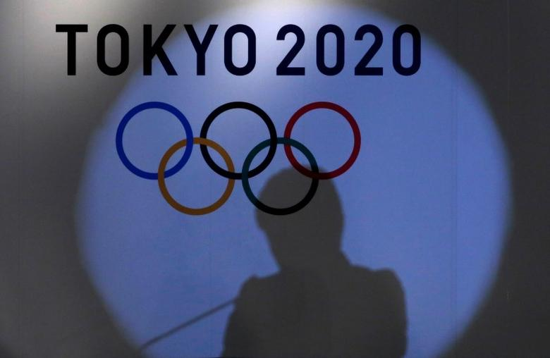 A shadow of of Tokyo governor Yuriko Koike is seen on the logo of Tokyo 2020 Olympic games during the Olympic and Paralympic flag-raising ceremony at Tokyo Metropolitan Government Building in Tokyo, Japan, September 21, 2016.  REUTERS/Toru Hanai/Files