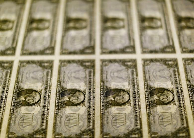 United States one dollar bills are seen on a light table at the Bureau of Engraving and Printing in Washington November 14, 2014. REUTERS/Gary Cameron/File Photo