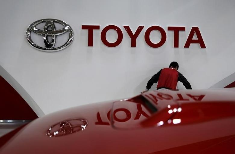 An employee works under a Toyota Motor Corp logo at the company's showroom in Tokyo, Japan February 5, 2016. REUTERS/Toru Hanai/File Photo
