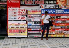 Un hombre habla por celular afuera de una tienda en un distrito comercial de Tokio, Japón. 29 de septiembre de 2016. Las ventas minoristas de Japón bajaron más que lo esperado en agosto, su sexto mes consecutivo de caídas interanuales por unas menores ventas de ropa y electrodomésticos, lo que mantiene la presión sobre las autoridades para que refuercen el gasto de los hogares. REUTERS/Toru Hanai