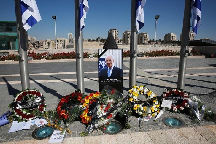 Wreaths are placed next to a portrait of former Israeli President Shimon Peres, as he lies in state at the Knesset plaza, the Israeli parliament, in Jerusalem September 29, 2016. REUTERS/Ronen Zvulun