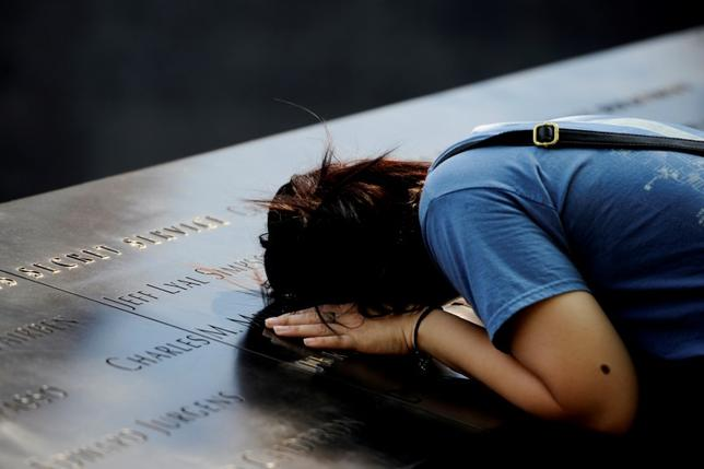 A woman lays her head on a row of names at the National September 11 Memorial, ahead of the 15th anniversary of the attacks in Manhattan, New York, September 10, 2016. REUTERS/Mark Kauzlarich