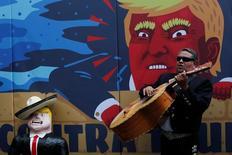 Музыкант играет на гитаре рядом с карикатурой на американского кандидата в президенты Дональда Трампа. Мехико, 25 сентября 2016 года. Мексиканский регулятор в четверг повысил на 50 процентных пунктов до 4,75 процента индикативную ставку в надежде уменьшить риск разгона инфляции из-за слабого песо, который инвесторы распродают из опасений, что новым президентом США станет Дональд Трамп. REUTERS/Carlos Jasso