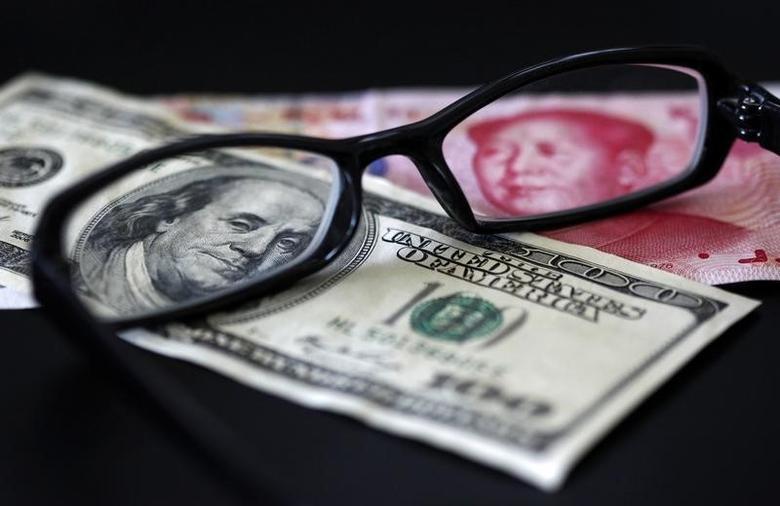 图为美元和人民币。REUTERS/Nicky Loh